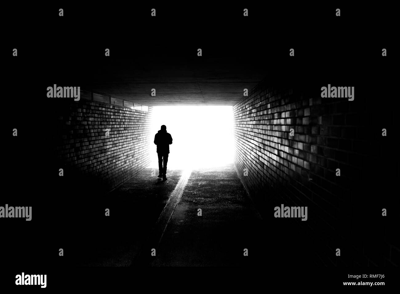 A man walking in a dark tunnel - Stock Image