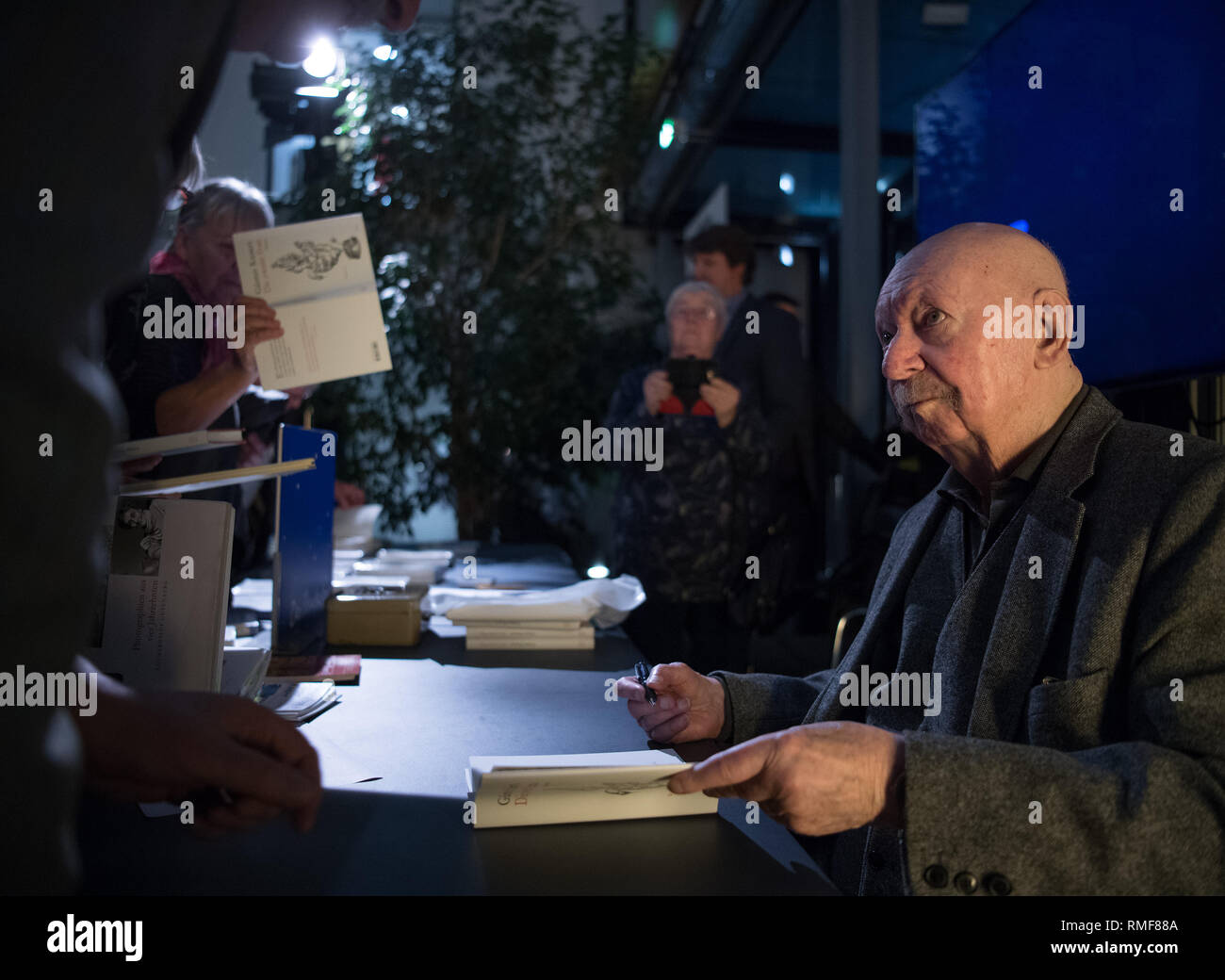 Berlin, Germany. 14th Feb, 2019. Writer Günter Kunert writes dedications in the state representation of Schleswig-Holstein after an interview about his book 'Die zweite Frau' (The Second Woman), which has now been published by Wallstein-Verlag. Kunert had written the novel almost 45 years ago, when he found the book unprintable in the GDR and had forgotten the manuscript in its hiding place. Credit: Soeren Stache/dpa/Alamy Live News - Stock Image