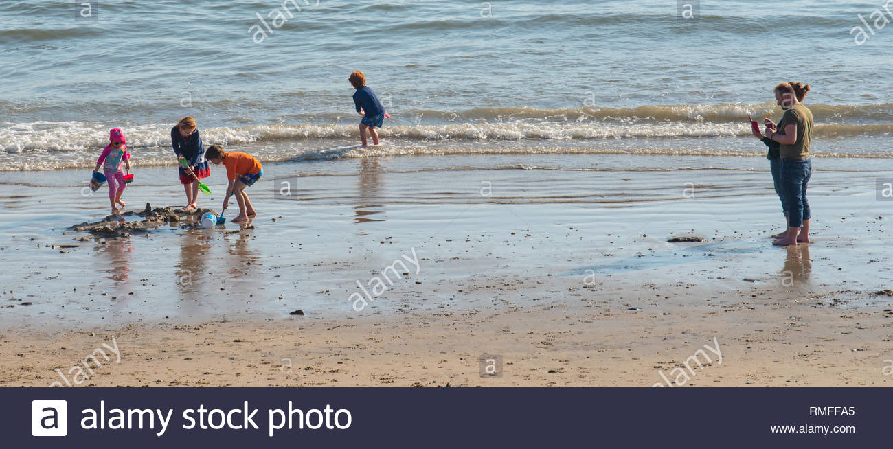 Lyme Regis, Dorset, UK. 15th February 2019. UK Weather: Picturesque Lyme Regis Basks in hot sunshine at the start of the half term getaway. Families enjoy a paddle in the sea on an unseasonably warm February day. Credit: Celia McMahon/Alamy Live News - Stock Image