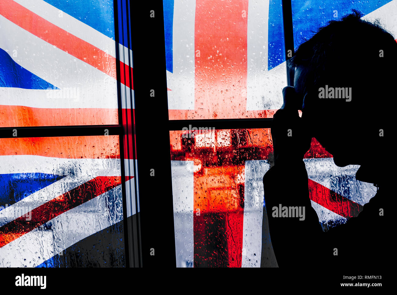 Mature man with hand on head near window on a rainy day with UK flag. Concept image for depression, male depression, mental health, male suicide... - Stock Image