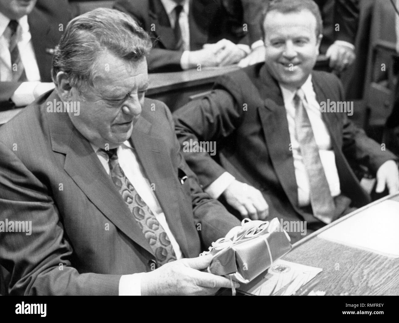 Bavaria's Prime Minister Franz Josef Strauss looks at a packet of contaminated hay from the Chernobyl disaster, which the Green parliamentary group presented to him in protest at the inaugural session of the Bavarian State Parliament. Right next to Strauss, Gerold Tandler, Group Chairman and CSU Secretary General. - Stock Image