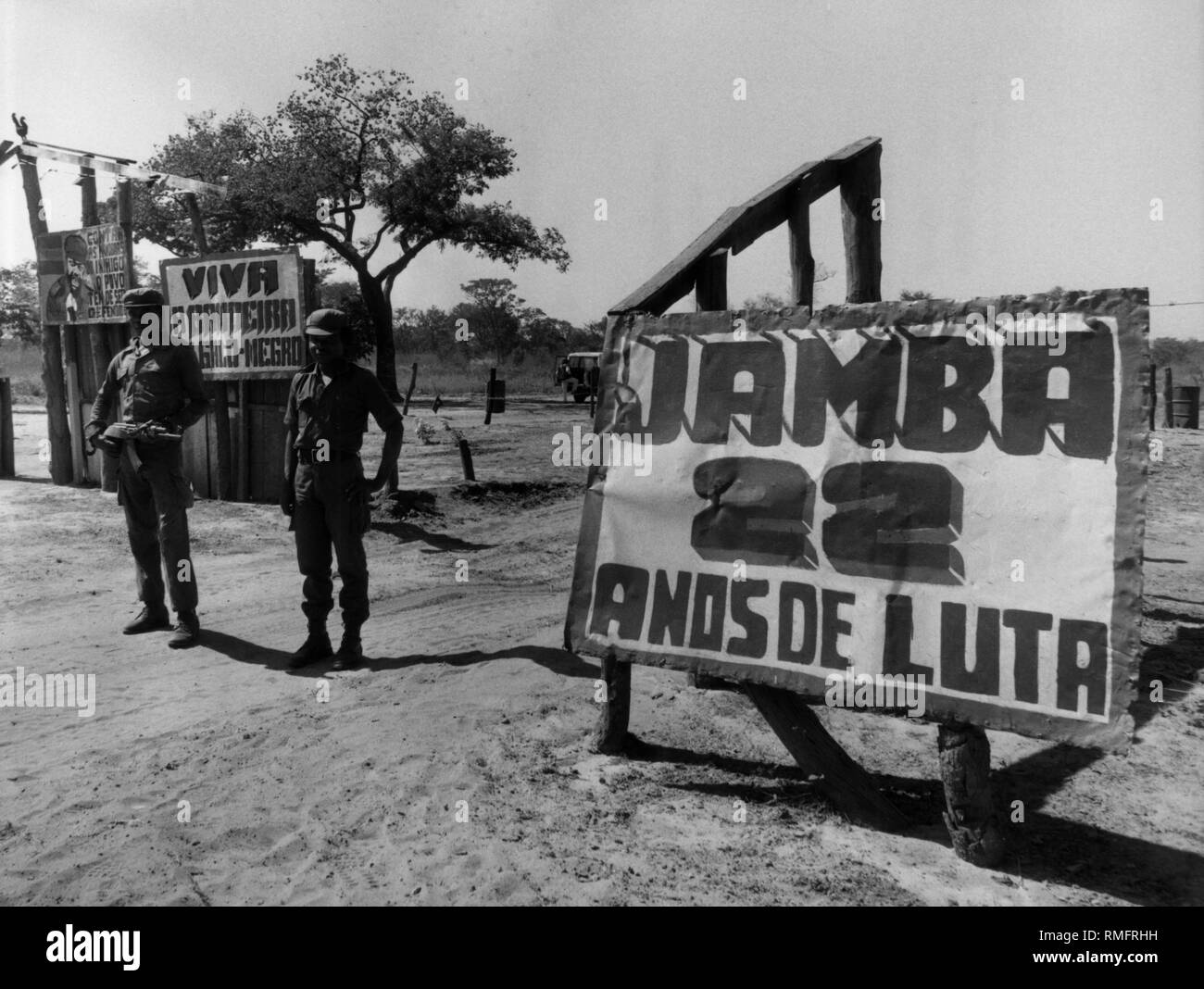 Armed UNITA guerrilla soldiers guard the entrance to their Jamba camp. On the left is a sign that points to the 22 years of civil war in Angola. - Stock Image