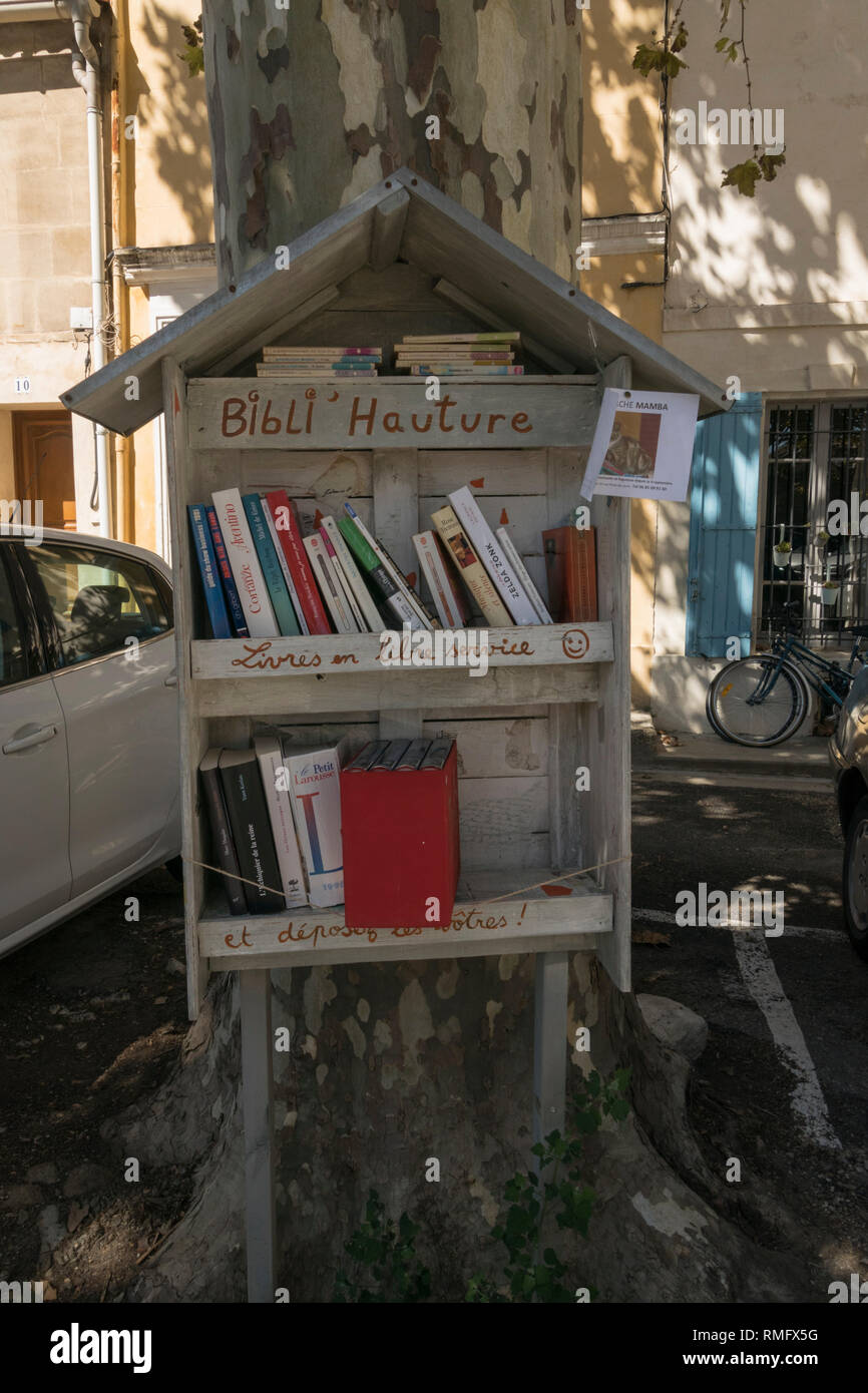 A handmade wooden book exchange creates a free community library service in Arles in the south of France - Stock Image
