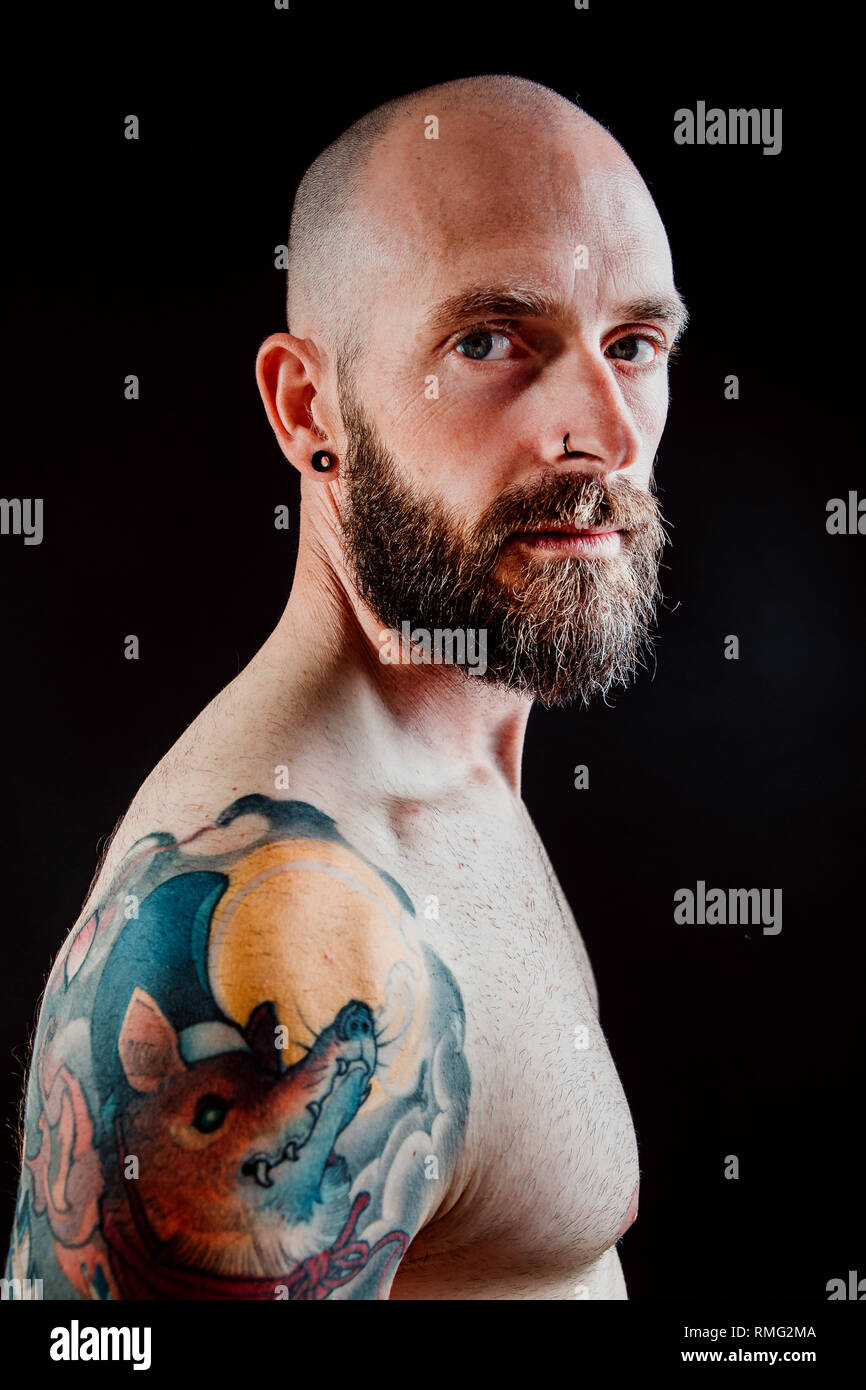 Side view of shirtless bald serious hipster with tattoos on hands looking at camera on black background - Stock Image