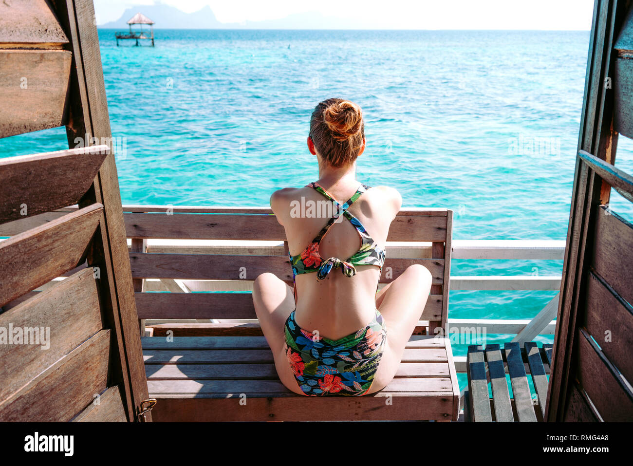 Back view of lady in swimsuit and sunglasses sitting on seat near blue sea in Jamaica - Stock Image