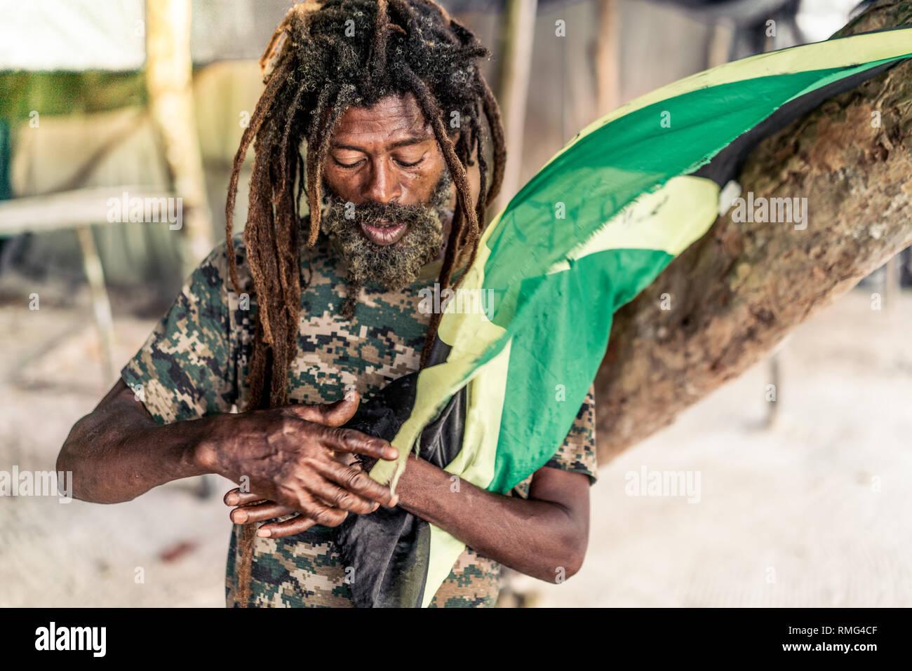 African American bearded male with dreadlocks holding Jamaica flag near tree - Stock Image