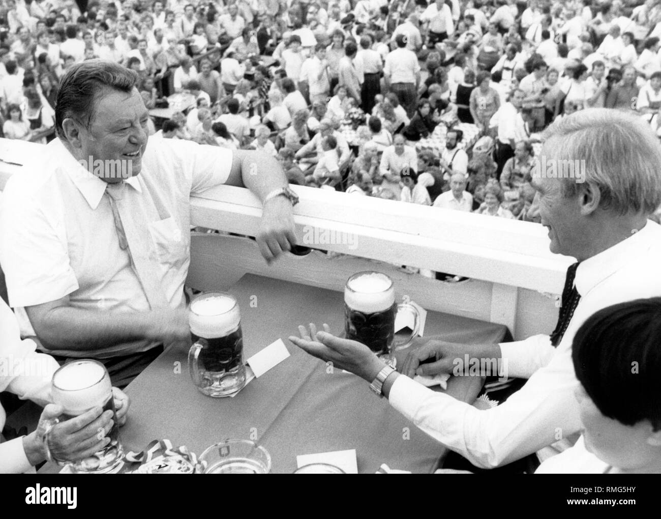 Bavarian Minister President President Franz Josef Strauss (left, CSU) is talking to the Mayor of Munich Georg Kronawitter (right, SPD), while having a liter of beer at the Oktoberfest in Munich. Stock Photo