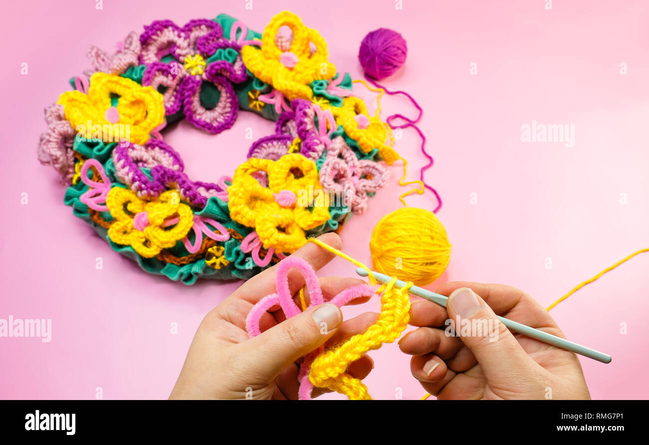 Flowers crocheting hands. Easy crafting for yellow wool yarn and pink pipe cleaner. A woman crafting free form wreath. - Stock Image