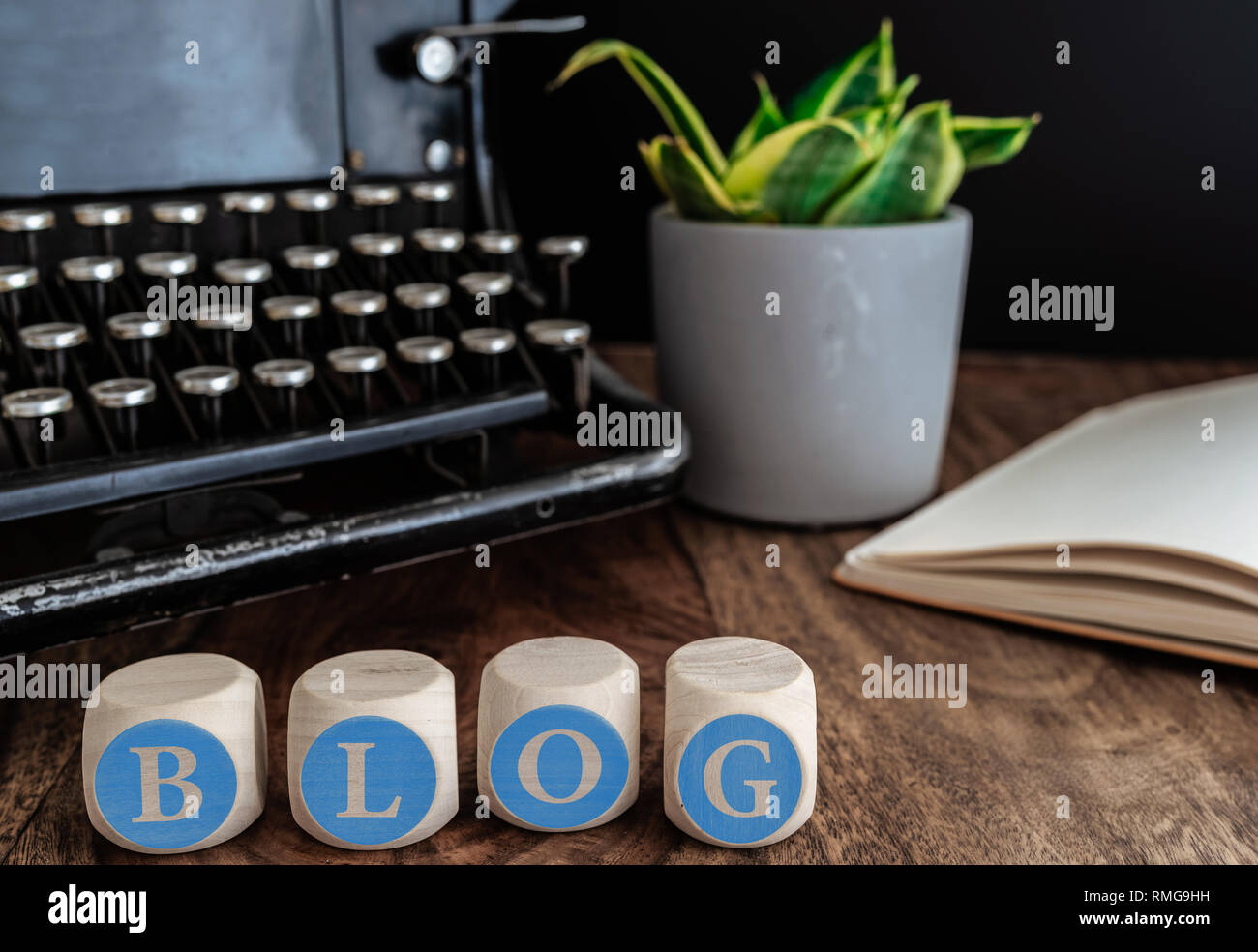 word BLOG on wooden blocks against vintage typewriter, potted plant and note pad on table - Stock Image