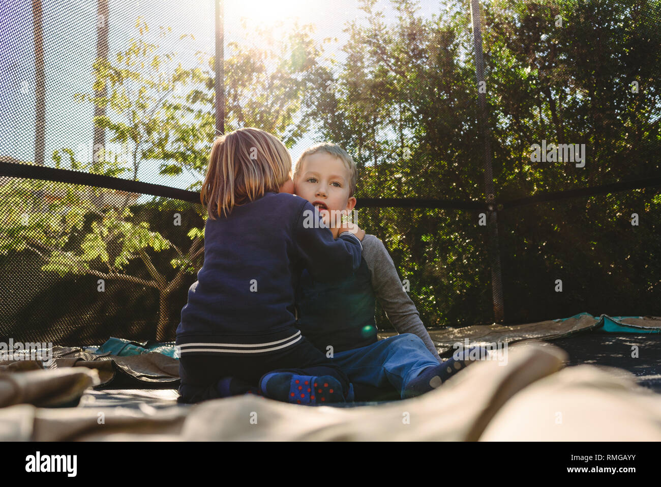 Two children friends accomplices plotting secret games in their spring break, friendship lifestyle concept in childhood. - Stock Image
