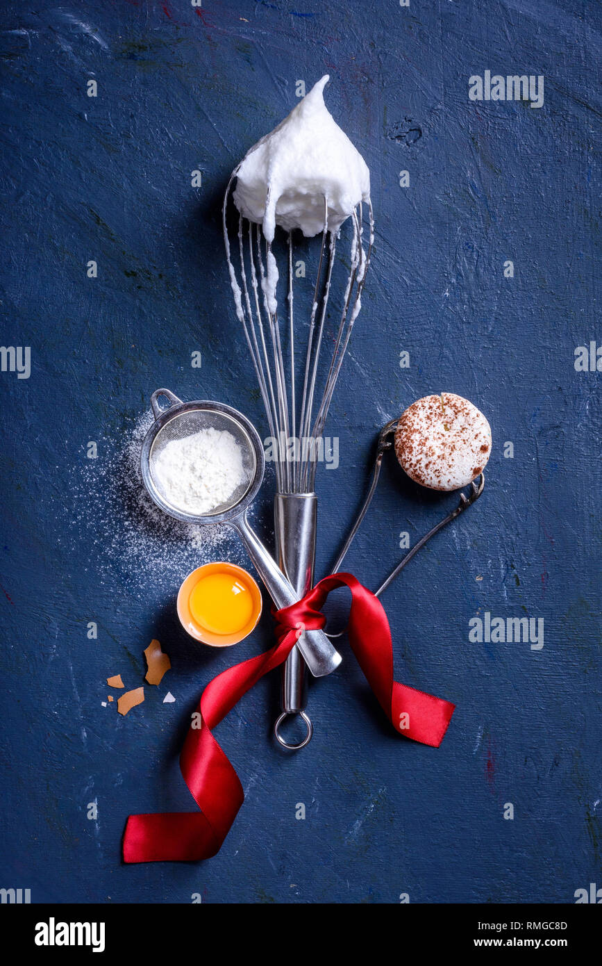 Baking or cooking background. Ingredients, kitchen items for baking cakes. Kitchen utensils, flour, eggs, macaroni dessert. New year, top view. Stock Photo