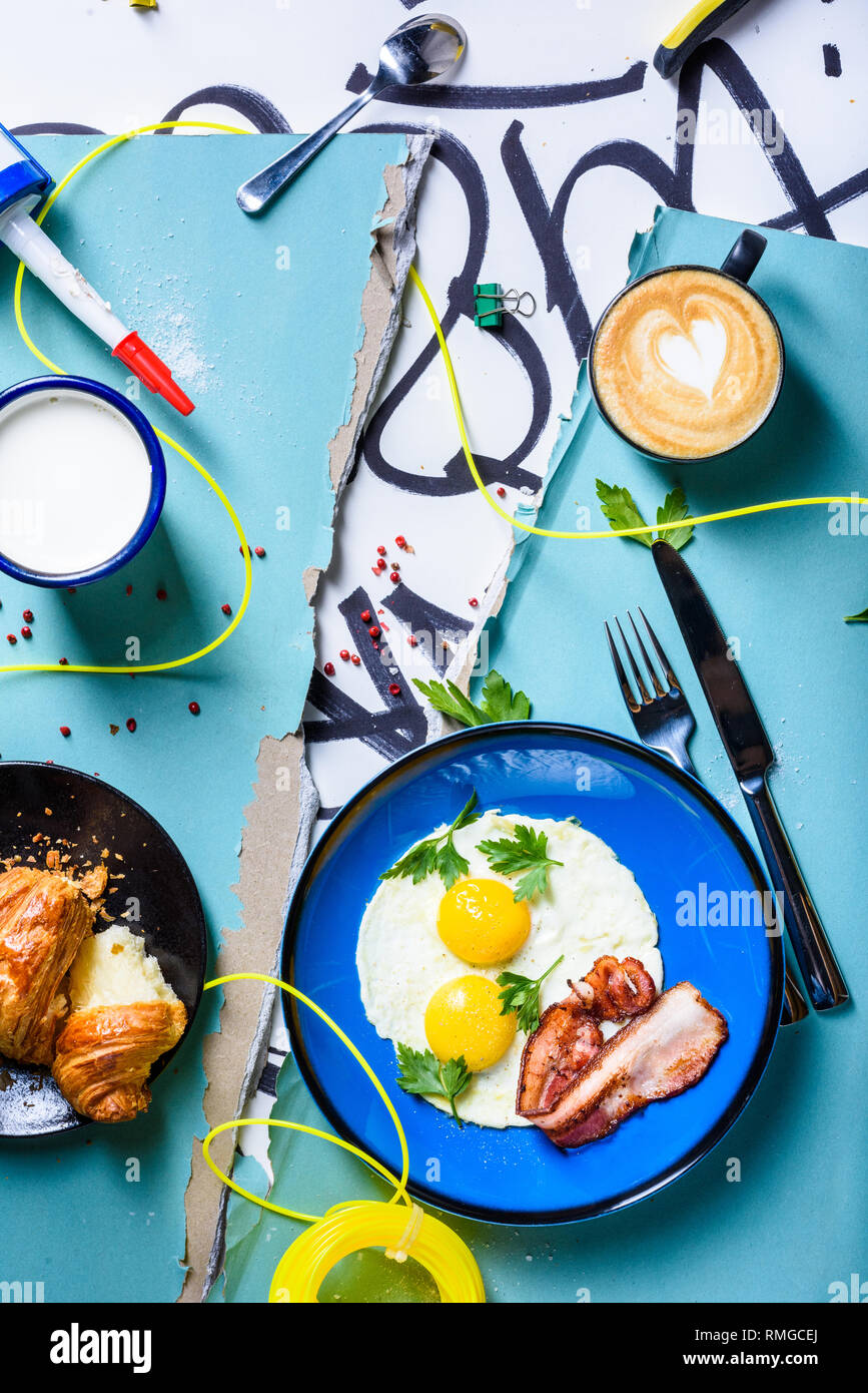 Fried eggs and bacon breakfast, served with coffee and croissant. Sunny side up eggs hipster style. Top view.The Art of food. - Stock Image