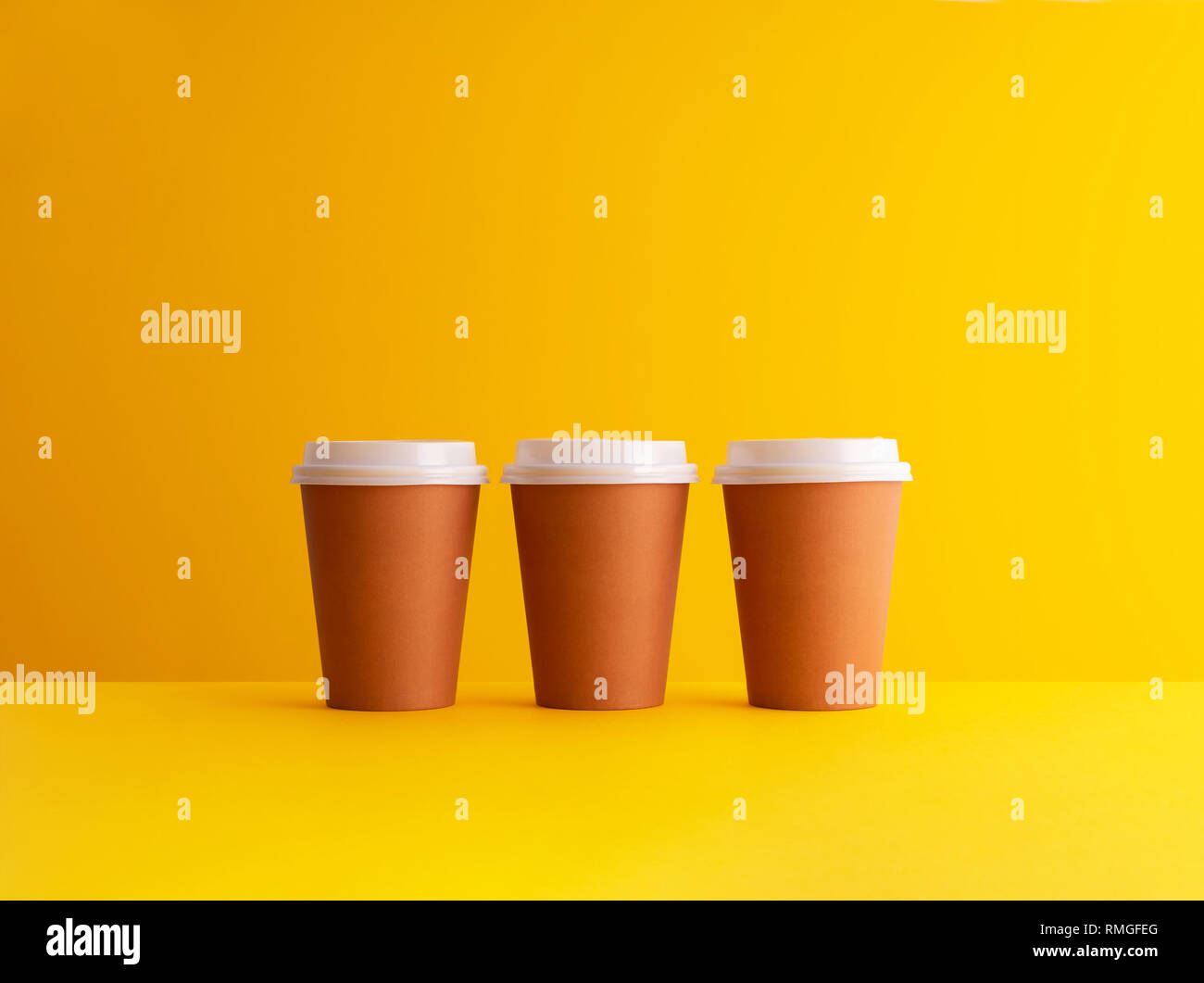 afc7bbfc752 Multiple disposable coffee cups organized in a row over yellow background -  Stock Image