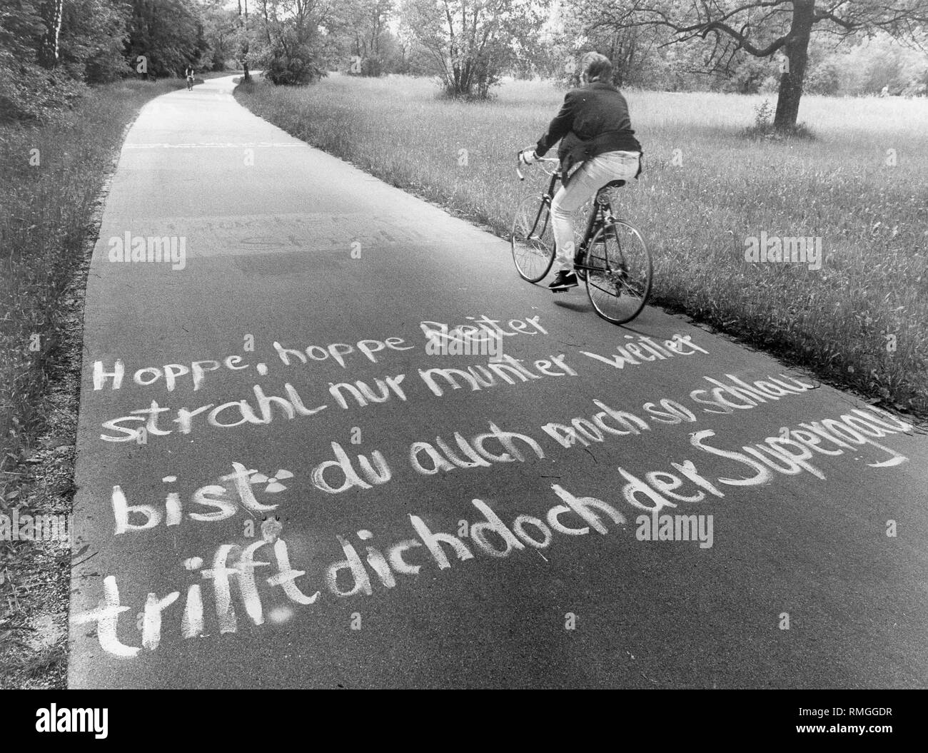 On the bike path along the east bank of the Isar: 'Hoppe, hoppe Reiter, strahl nur munter weiter / bist Du auch noch so schlau / trifft dich doch der Supergau'. (English translation:'Hop, hop rider, beam cheerfully on / you are still so smart / but the disaster will meet you'.) - Stock Image
