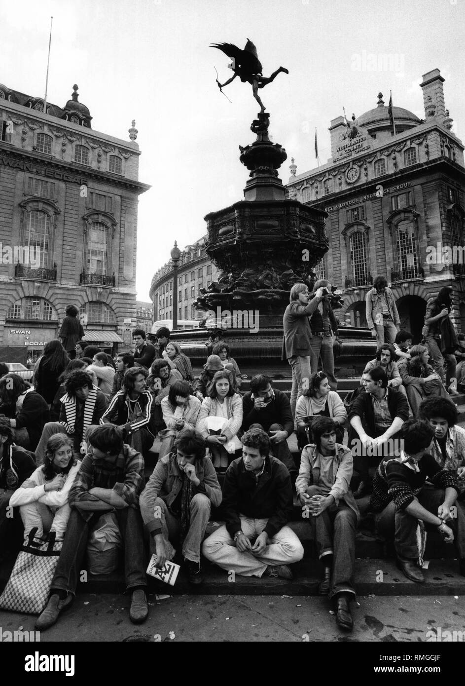Tourists sit on the steps of the Shaftesbury Memorial Fountain on Piccadilly Circus in London. - Stock Image