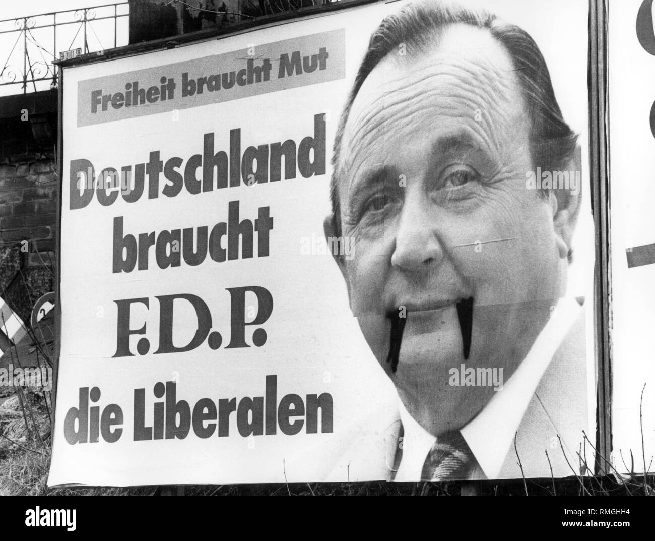 An election poster of the FDP was defaced. On the image of the FDP chairman Genscher vampire teeth were painted. The election poster of the FDP advertises 'Freedom needs courage, Germany needs F.D.P. the Liberals'. - Stock Image