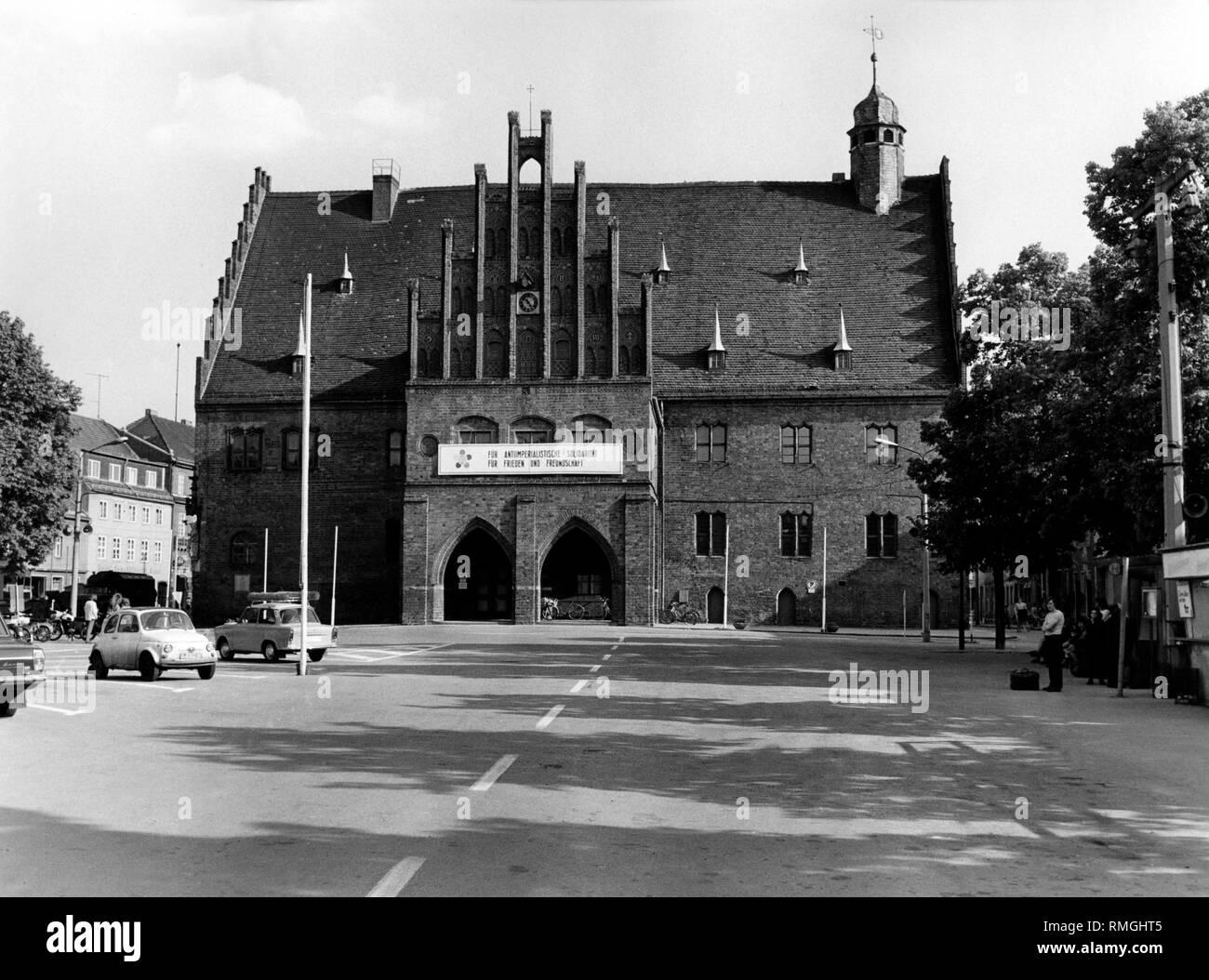 View of the brick Gothic Town Hall with the inscription 'For anti-imperialist solidarity, for peace and friendship' to celebrate the Xth World Festival of Youth and Students in Berlin 1973 on the market square in Jueterbog, Brandenburg. - Stock Image