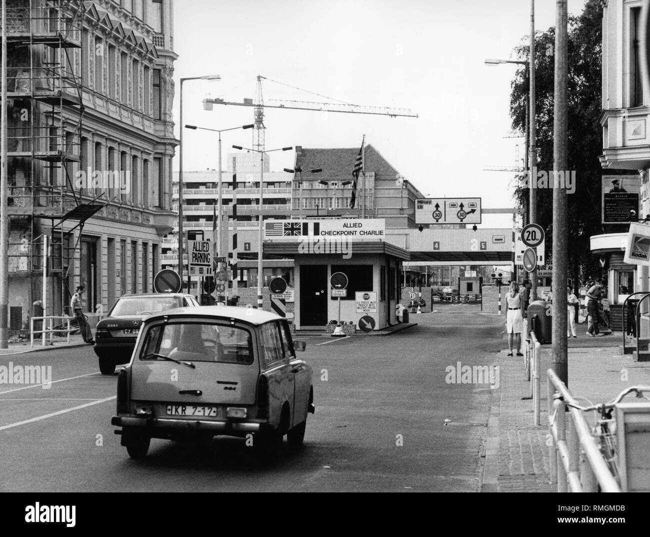 View along the Friedrichstrasse on the Allied border posts with some vehicles, passers-by and border guards. - Stock Image