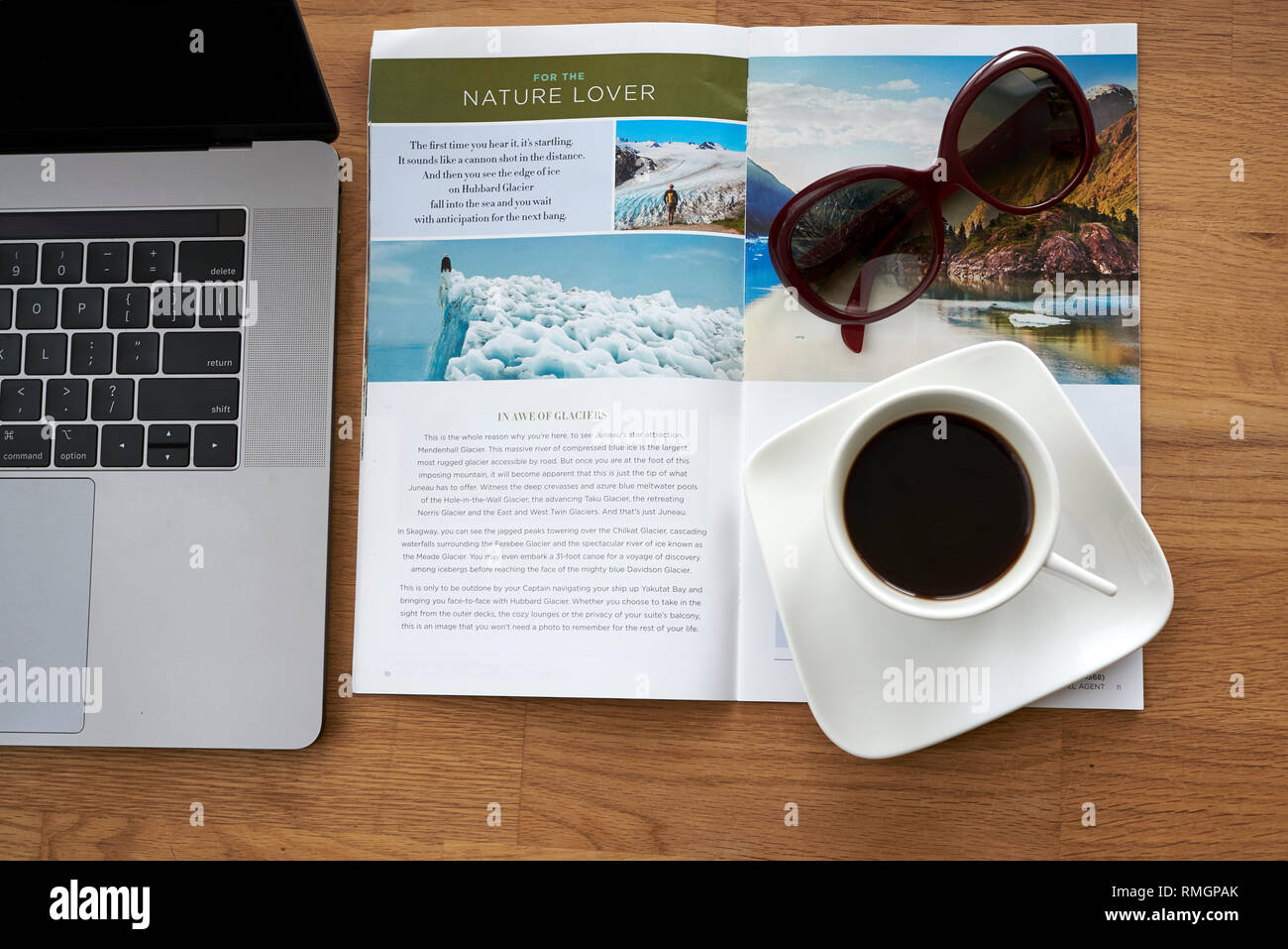 Travel section in a newspaper - planning holiday and new adventure in Alaska. Coffee, sunglasses, brochure and laptop on wooden table. - Stock Image