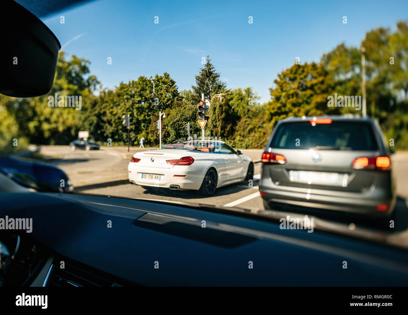 STRASBOURG, FRANCE - SEP 15, 2018: Driver pov at the intersection with luxury white convertible BMW car focus from tilt-shift lens - Stock Image