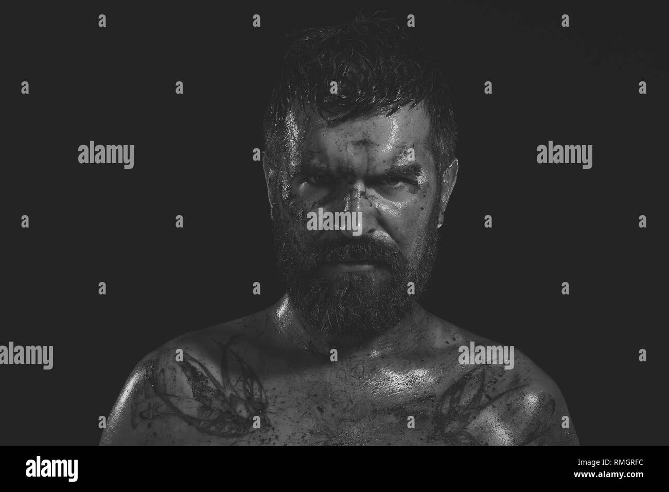 Bearded hipster with tattoo on chest on black background - Stock Image