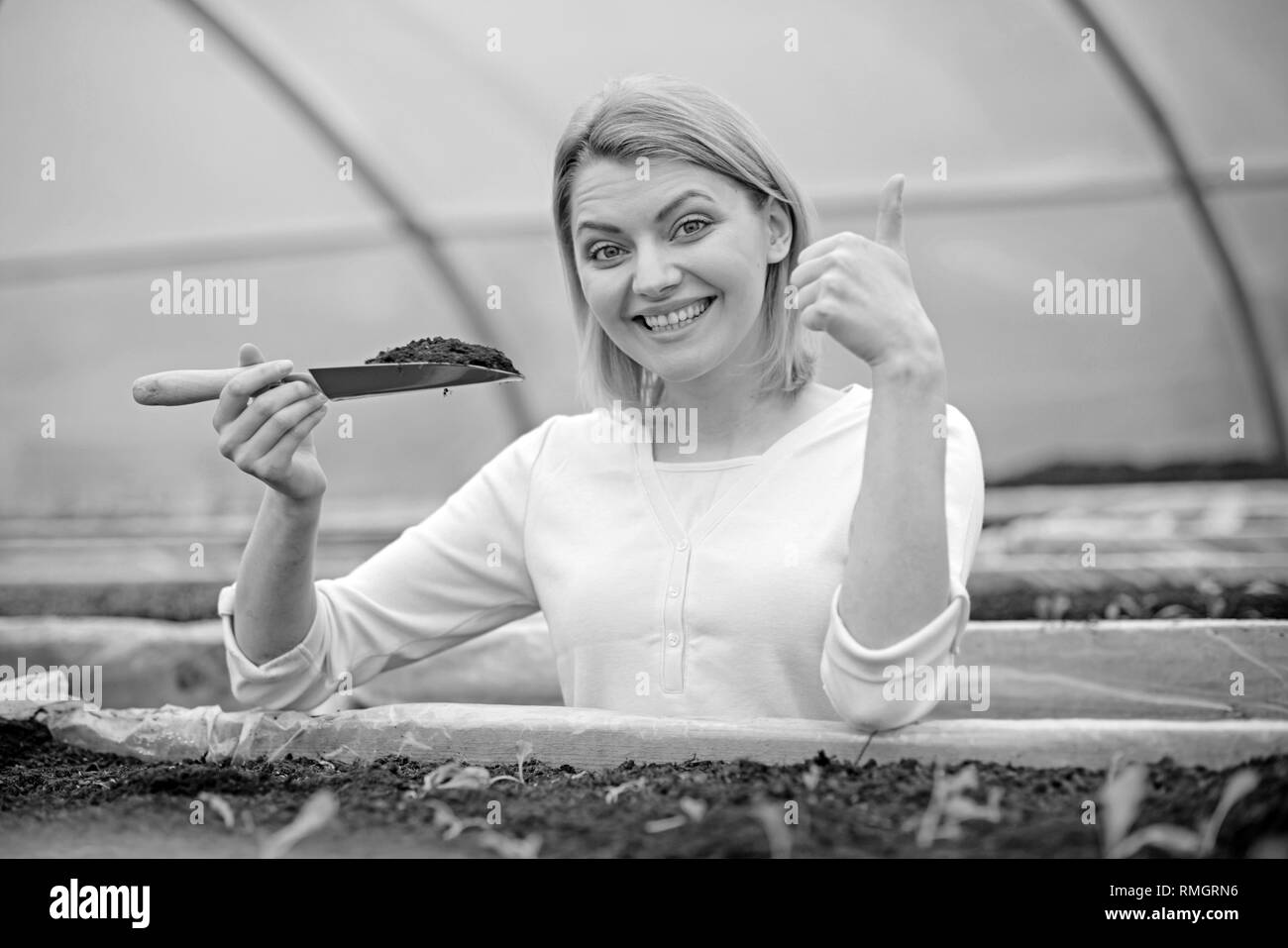 Smiling lady in pink cardigan working in greenhouse. Blond
