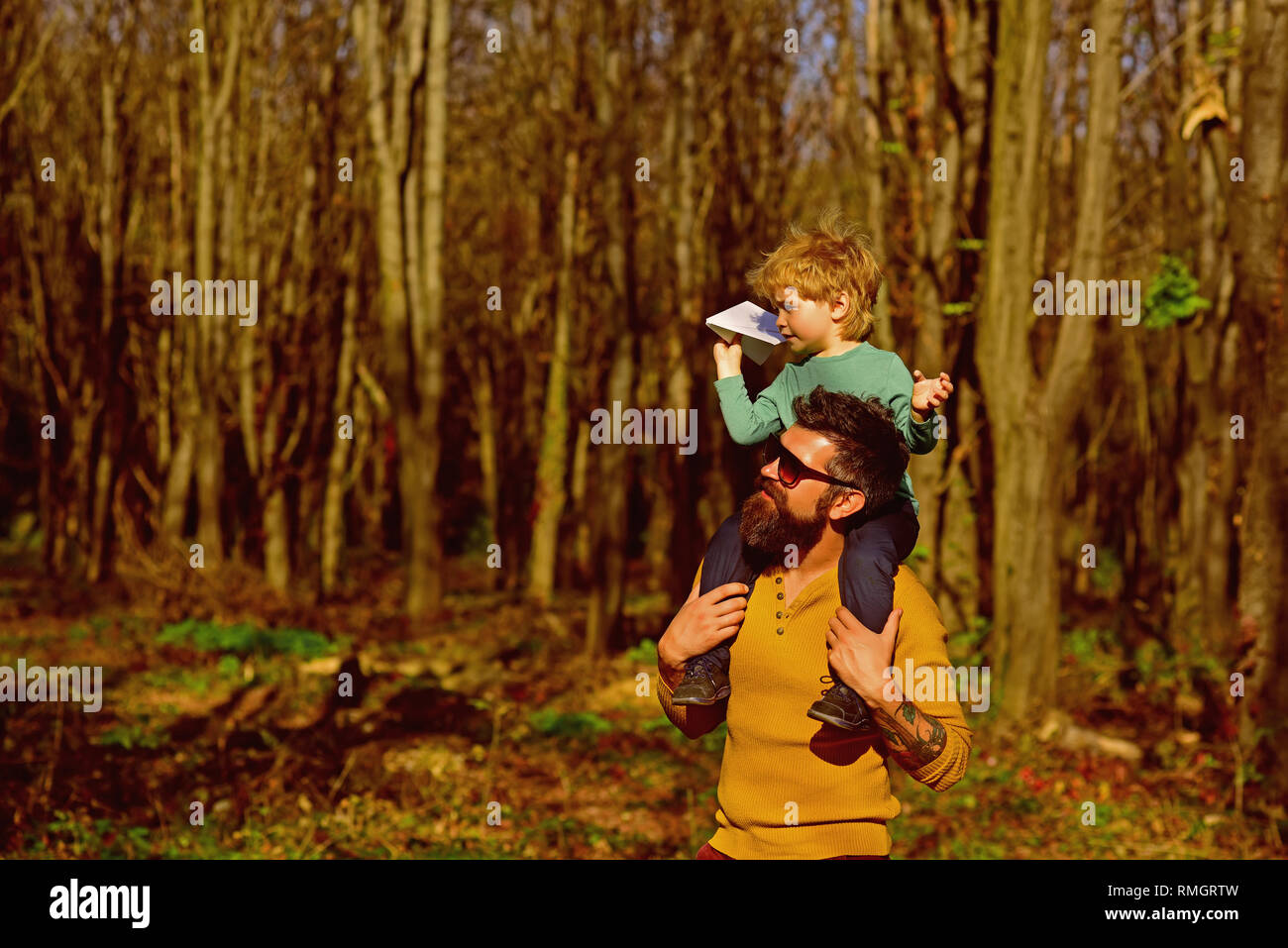 Pleasure is a path to joy. Father give little child piggybacking in pleasure park. Father and son spend time together - Stock Image
