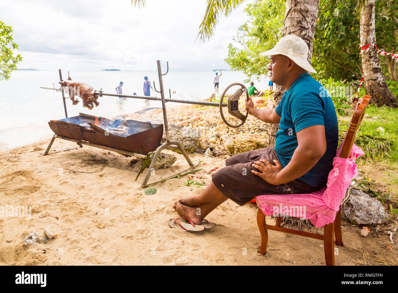 Tongatapu, Tonga - Jan 10 2014: a local native indigenous Polynesian man does a pork barbecue of a small piglet on an open fire of a home-made grill m - Stock Image
