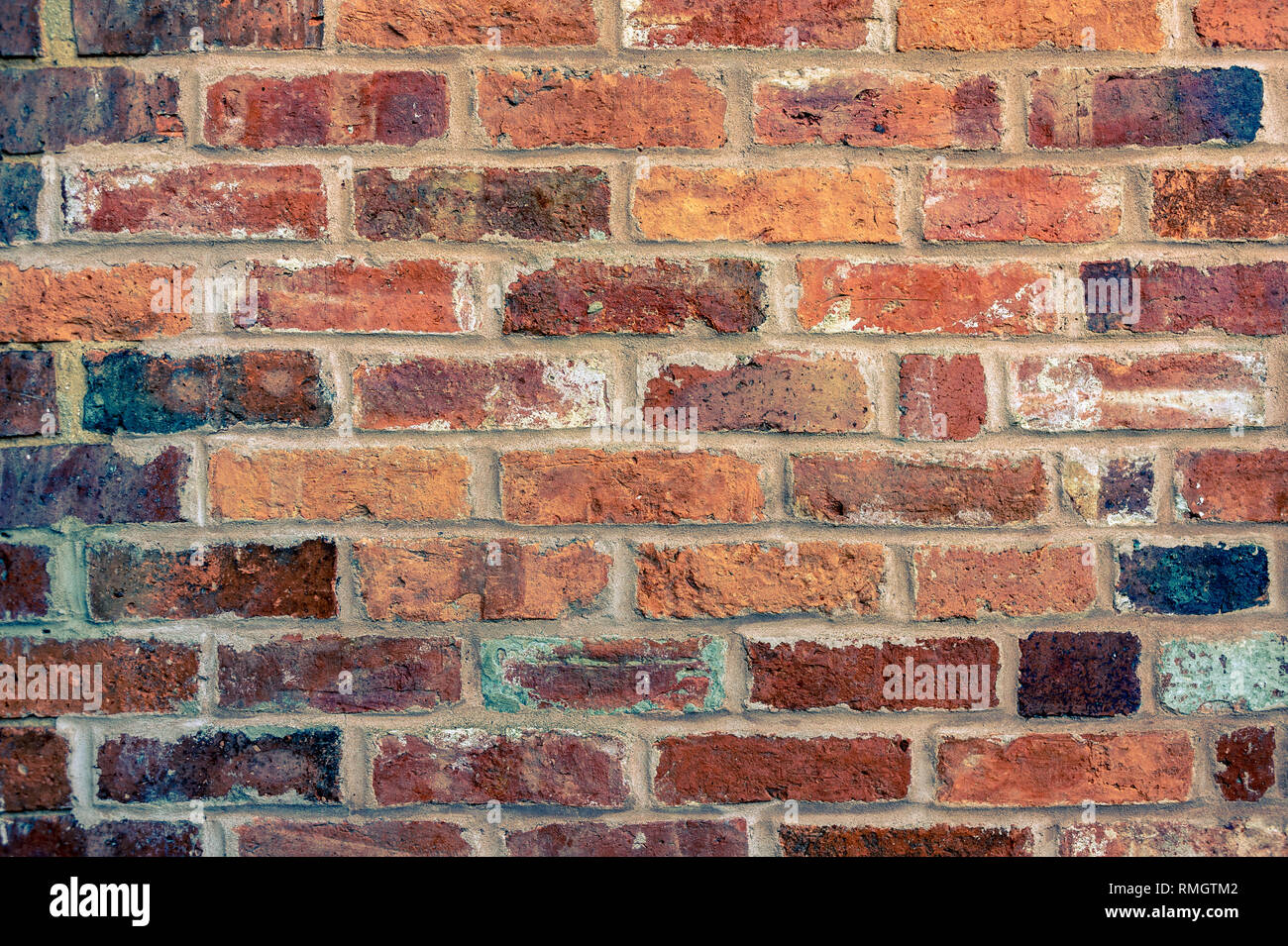 A brick wall built with old bricks which has been duo toned in yellow and blue - Stock Image
