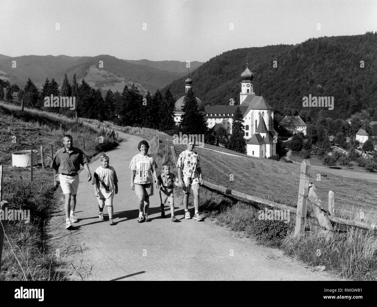 A family on a trail in the region between Belchen and Schauinsland in the Black Forest. In the background thie church of Münstertal. Undated picture. - Stock Image
