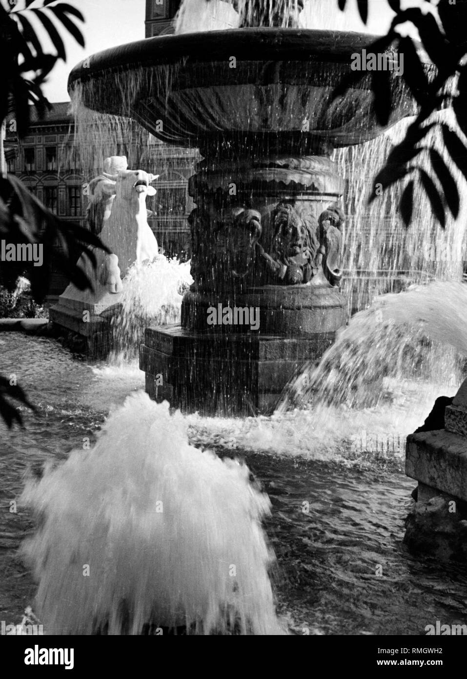 The Wittelsbacher Brunnen (fountain) at the Lenbachplatz in Munich. On the left-hand side a man on a horse. - Stock Image