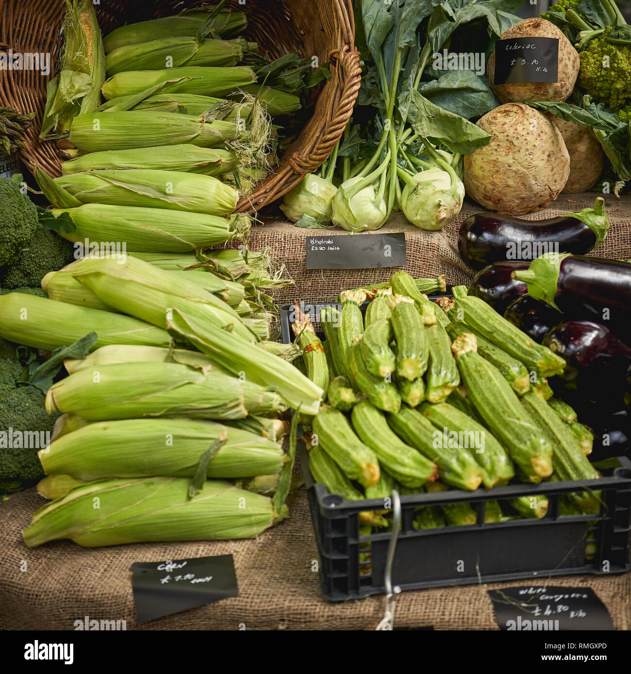 Green groceries including courgettes, aubergines, asparagus, red peppers and broccoli on sale at a vegetables stall in a local farmer market. Stock Photo