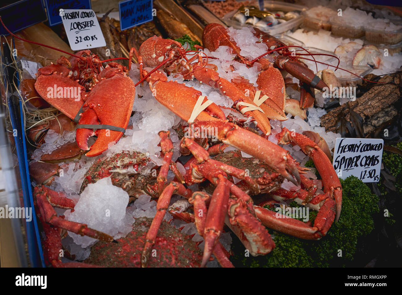 Shellfish including lobsters and crabs on sale at a fishmonger in a local food market. Landscape format. - Stock Image