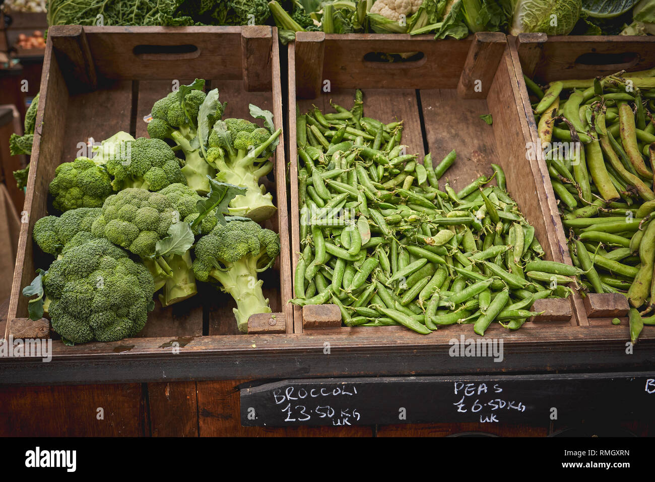 London, UK - June, 2018. Green groceries including courgettes, aubergines, asparagus, peppers and broccoli on sale at a vegetables stall in a market. Stock Photo