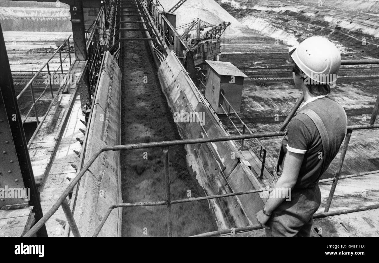 A worker looks at a conveyor belt on which lignite is being transported in July 1990. - Stock Image