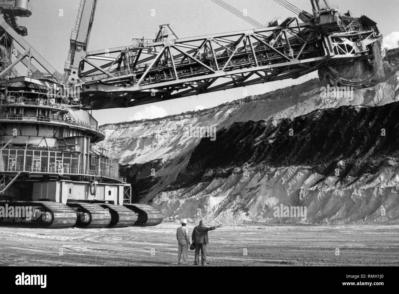 A bucket wheel excavator in the open pit mine at Bergheim near Juelich. In the foreground are two workers. - Stock Image