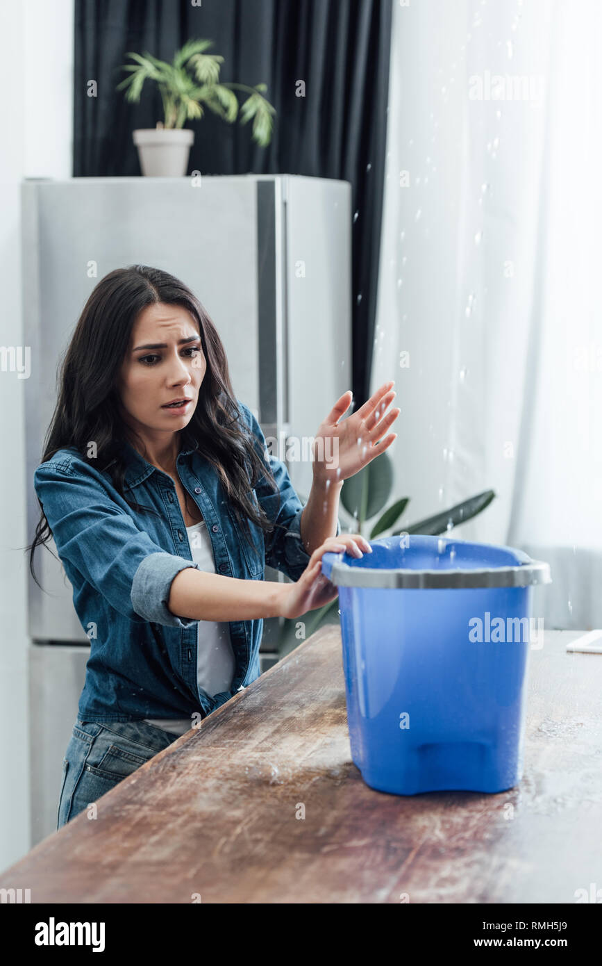 Worried woman using bucket during leak in kitchen Stock Photo