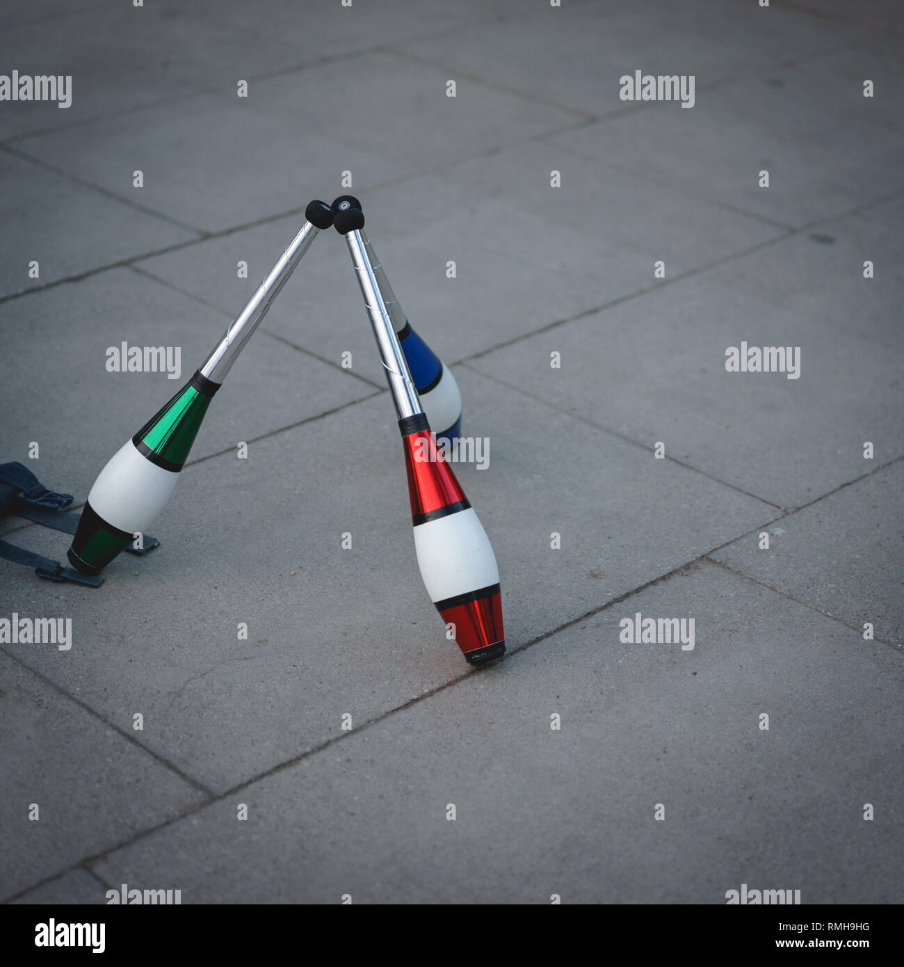 Three red, green and blue juggling clubs on a pavement. Square format. - Stock Image
