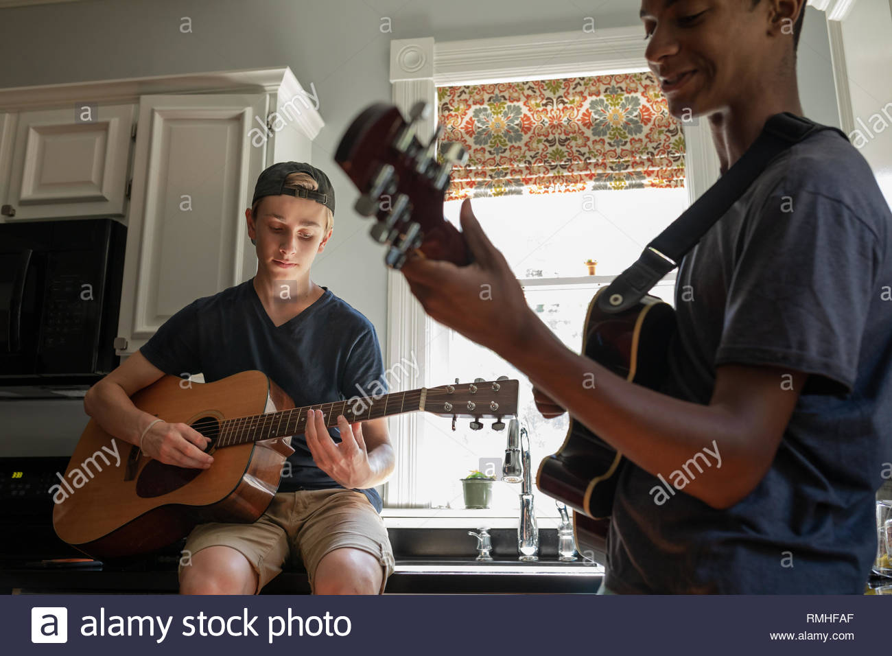 Two teenage boys playing guitars in the ktichen after school - Stock Image