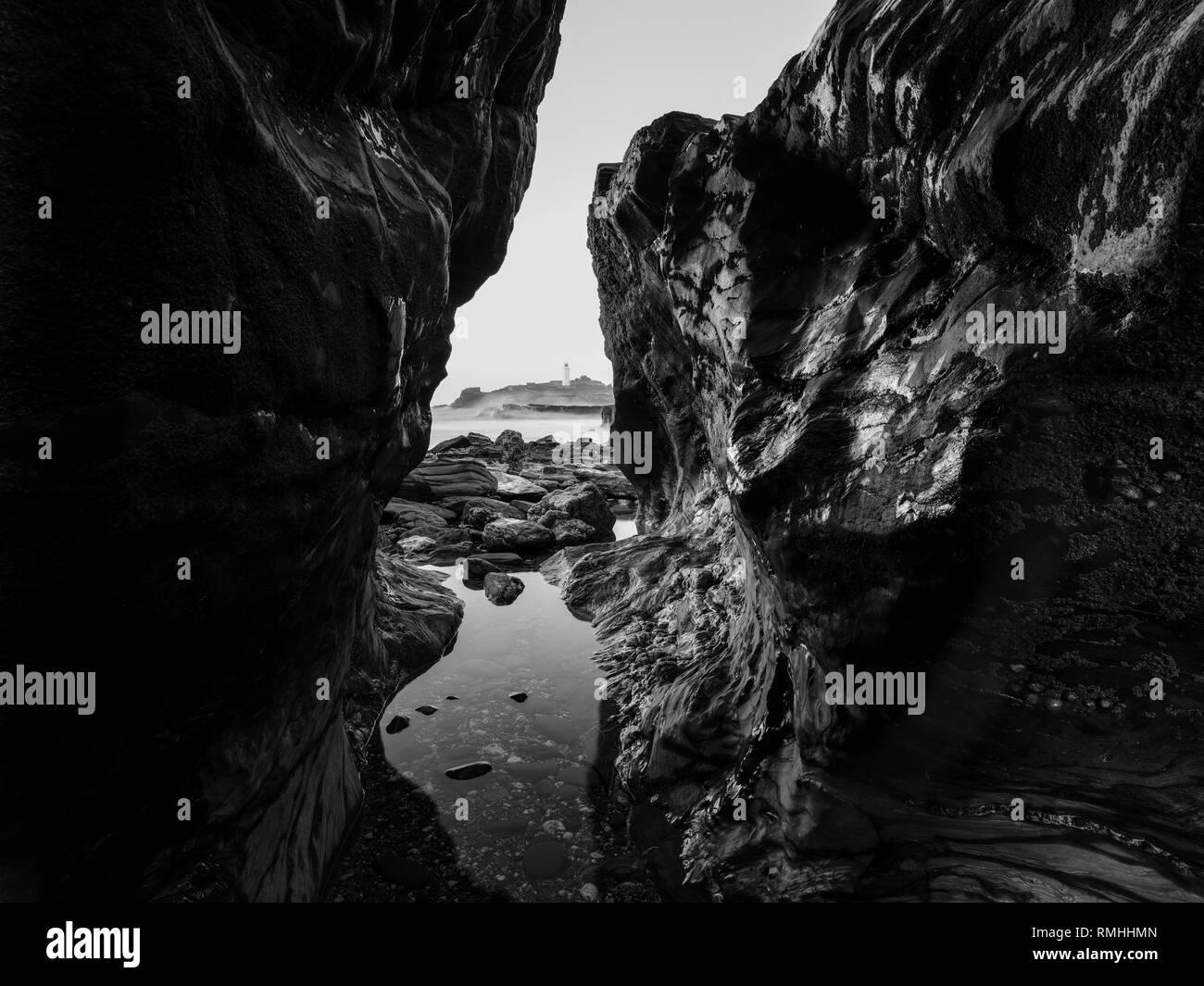 Godrevy Rocks View through rugged rocks towards Godrevy Lighthouse - Stock Image