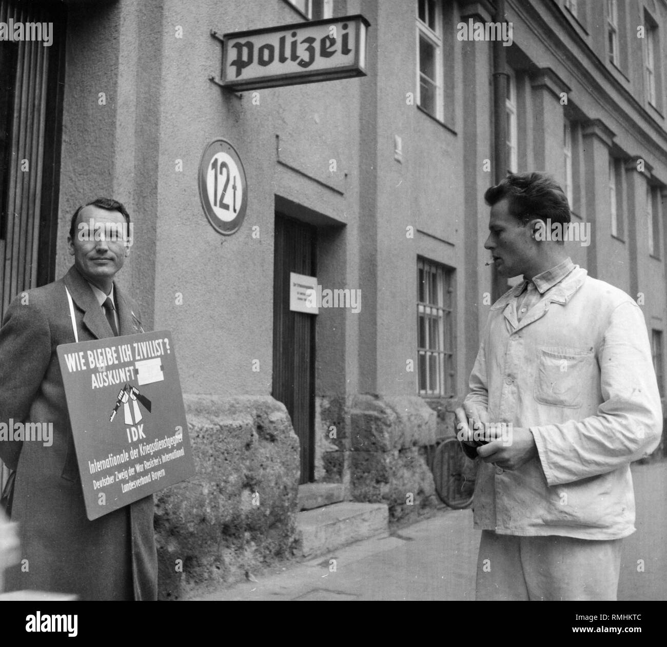 A representative of the IDK, the Internationale der Kriegsdienstverweigerer (Conscientious Objectors' International) stands with his poster in front of the registration office of the Bundeswehr in the Ettstrasse in Munich. Stock Photo
