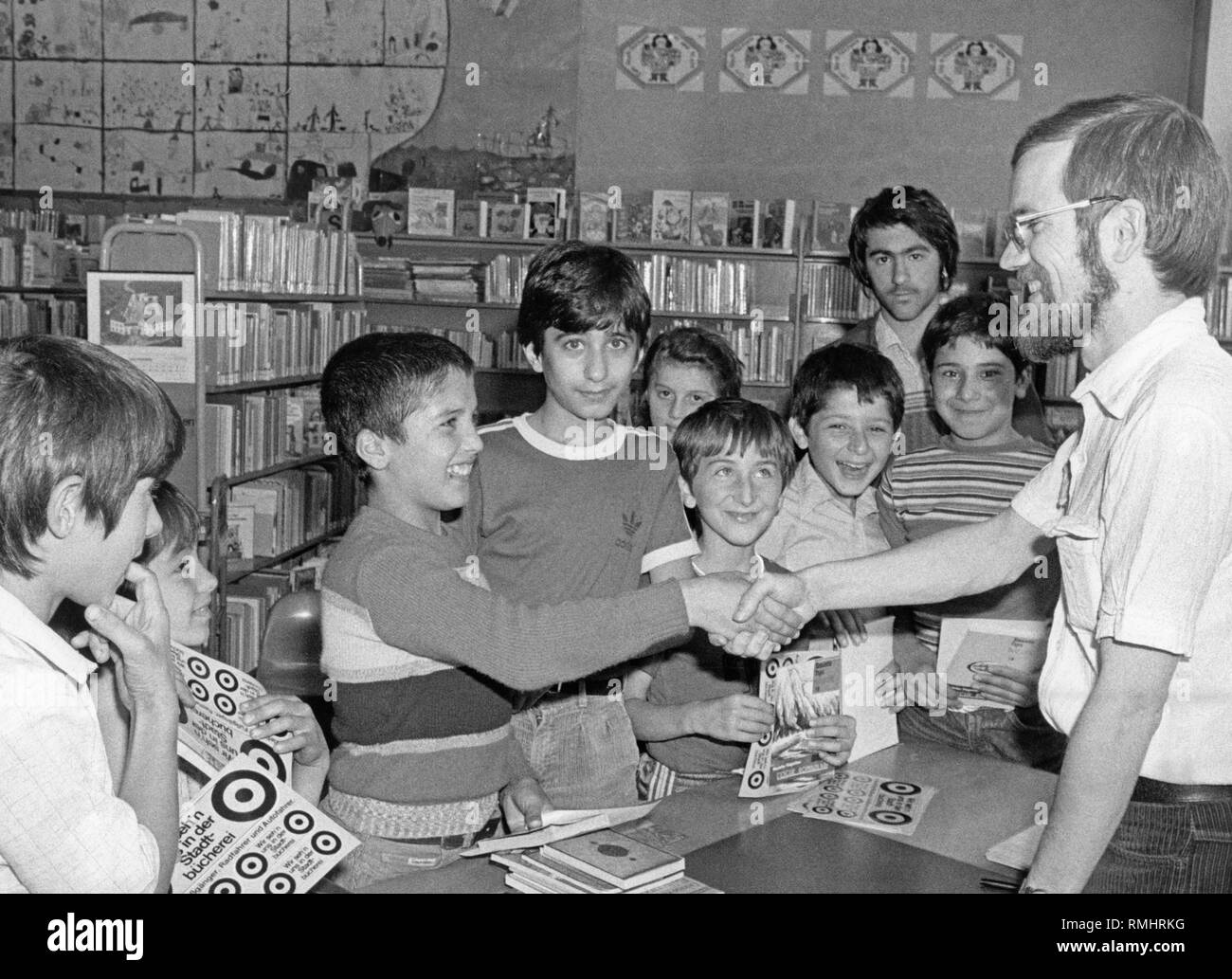 Hans-Peter Laqueur (far right) awards clever Turkish quiz participants at a ceremony at the youth library in Munich-Haidhausen (around 1980).  With the help of a children's non-fiction book,  previously the puzzlers had to answer 15 tricky questions. - Stock Image