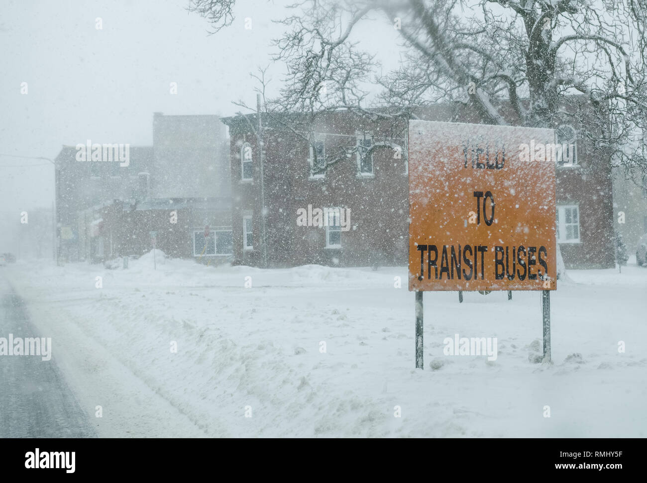 On Downie Street in Stratford, Ontario, we see a traffic sign that asks us to yield to transit buses that exit the terminal. Storm squall in winter. - Stock Image