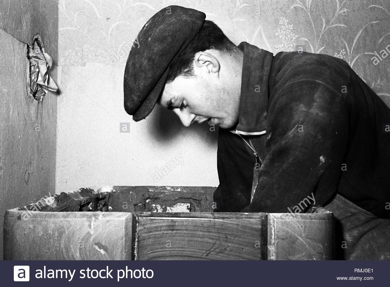 A stove farmer stove fitter puts a tiled stove in a flat in Zschopau in the federal state Saxony in the area of the former GDR, German democratic republic. Foto: Siegfried Bonitz - Stock Image