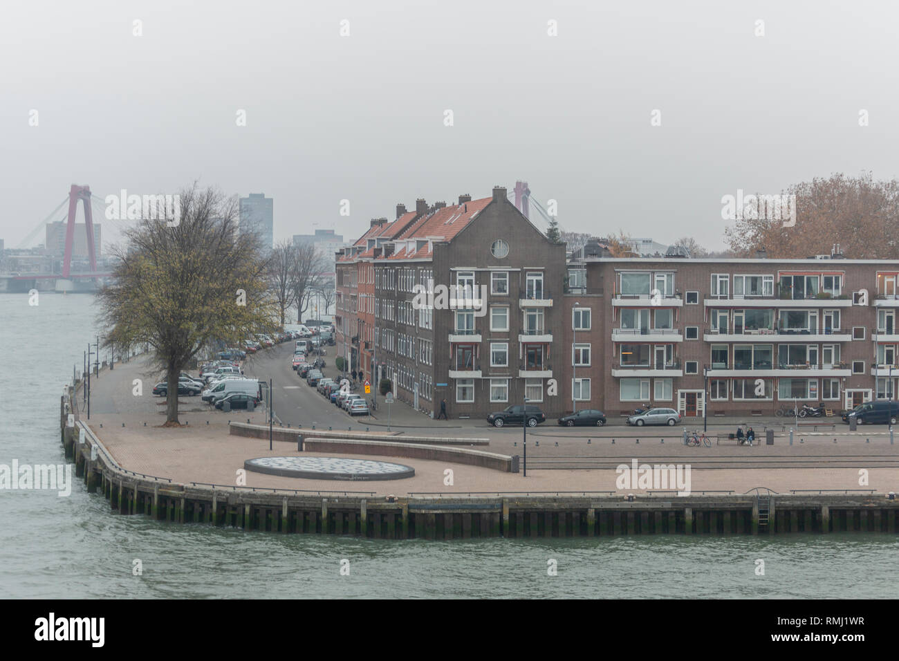 Neighbourhood quay in the city centre of Rotterdam on a hazy overcast day with in the background a bridge and city constructions - Stock Image