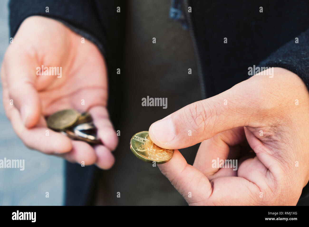 closeup of a young caucasian man on the street with some czech koruna coins in his hands - Stock Image