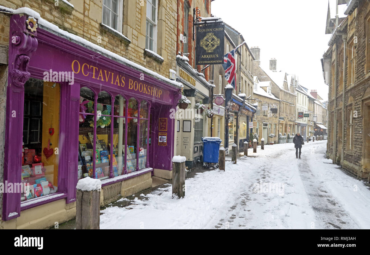 View up Black Jack Street, Octavias Bookshop, to Church of St. John Baptist, winter snow Cirencester town centre, Gloucestershire, England, GL7 2AA - Stock Image