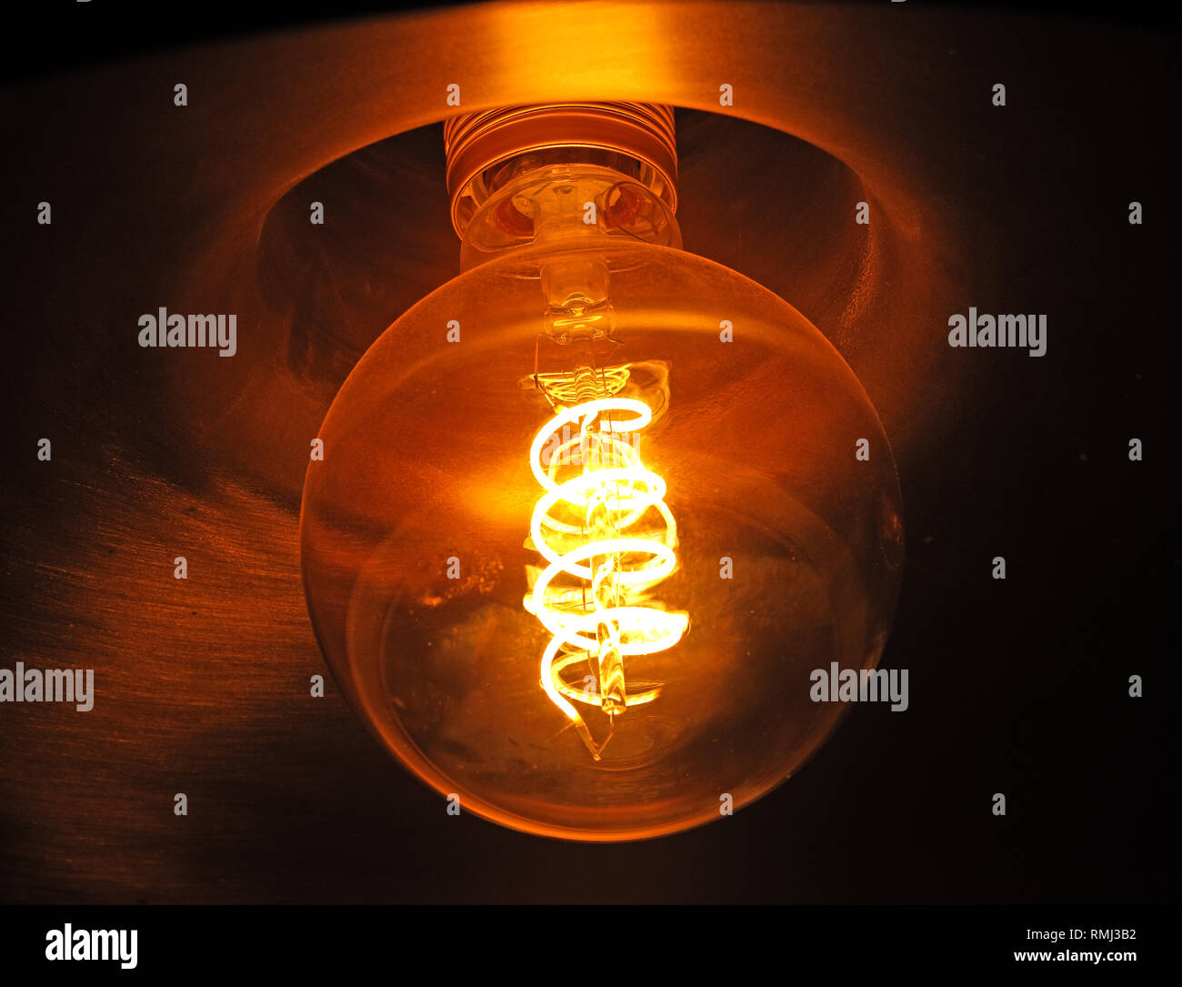 An incandescent electric light bulb, showing glowing filament, banned now in a number of countries, replaced with low energy and LED  bulbs - Stock Image