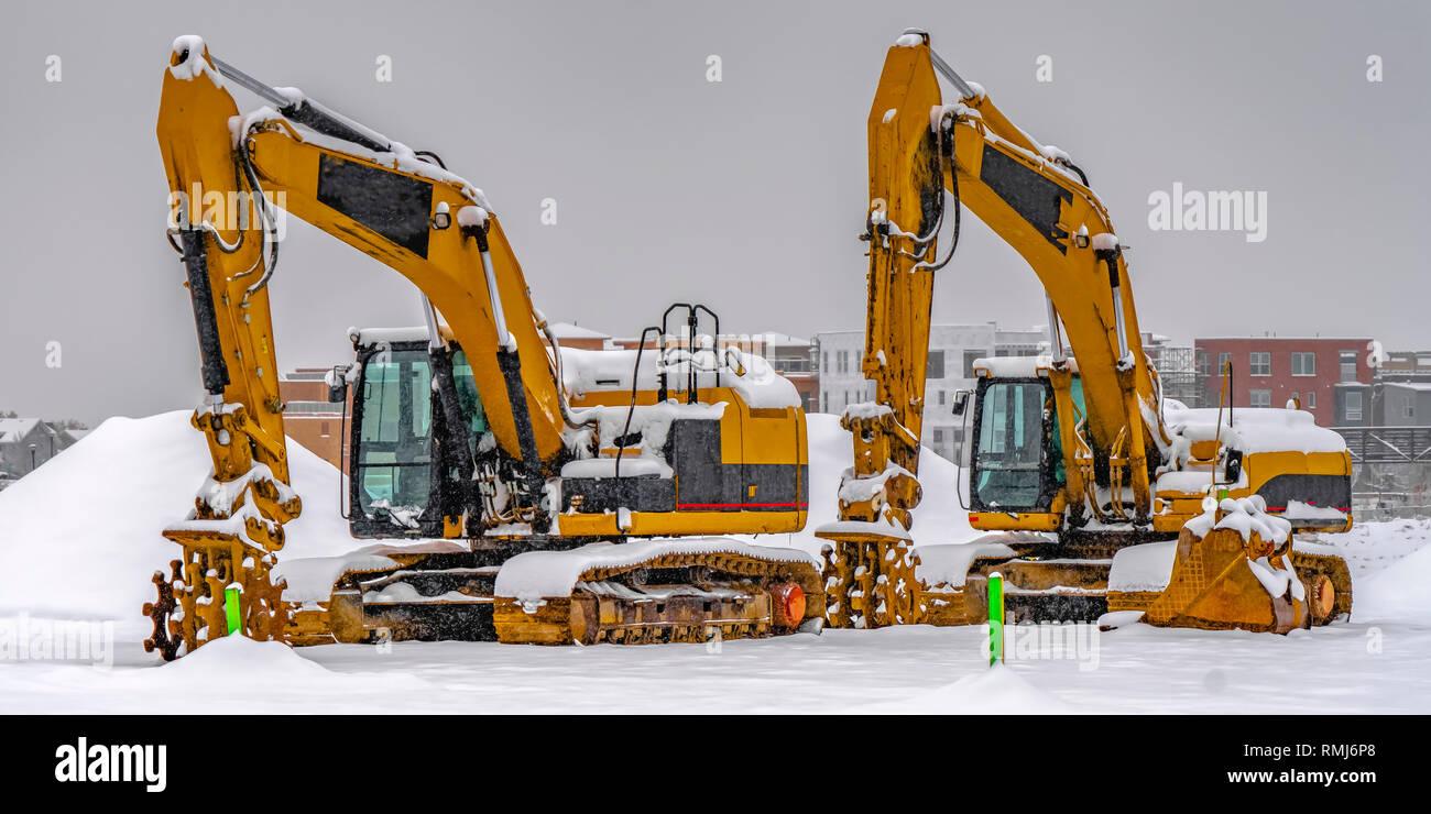 Excavators against snow and buildings in Daybreak - Stock Image
