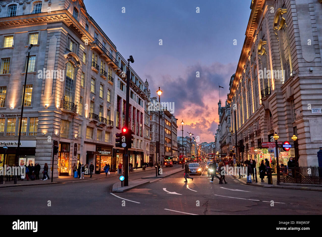 Rush hour and traffic near Piccadilly Circus with pedestrians walking in London's West End. Typical urban scenery in the center of London city. - Stock Image